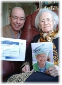 Cantor Heller visits Annelise Winter who holds her birthday card from the Queen.